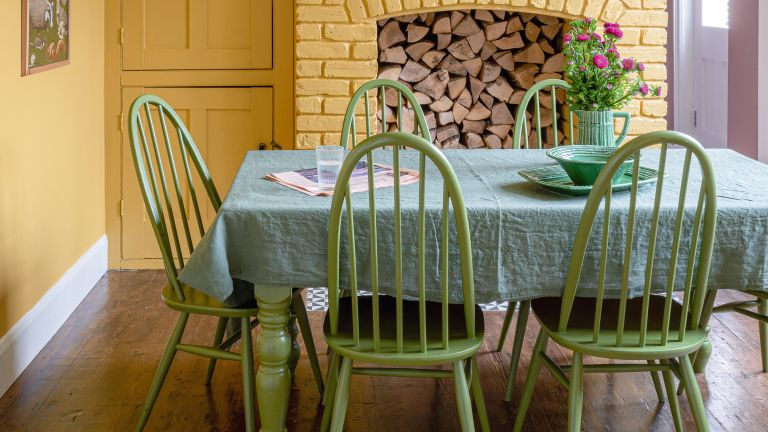 Green and yellow dining room with brick fireplace