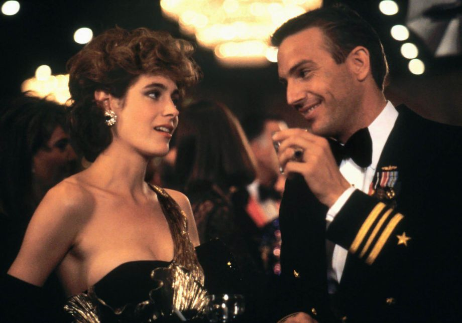 Sean Young and Kevin Costner flirt at a party