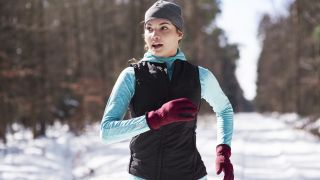 A woman dressed for winter runs in the snow