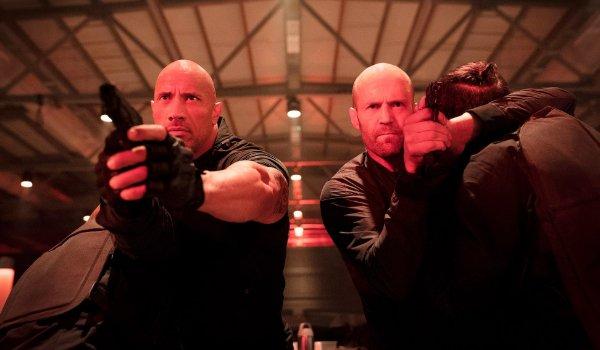 Hobbs and Shaw aiming their guns in a warehouse