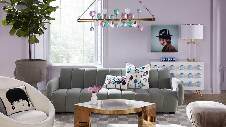 Jonathan Adler designed lavender room with gray sofa and artwork