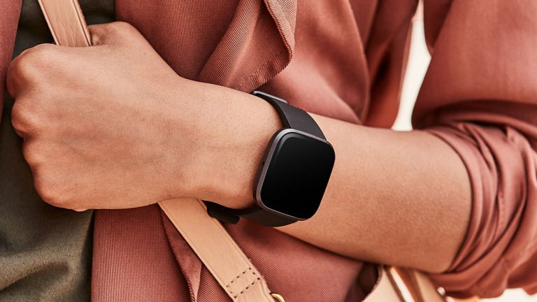 The best Fitbit versa 2 on woman's wrist wearing pink holding bag
