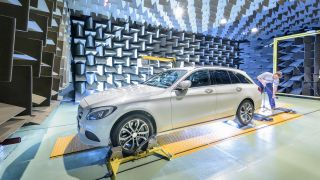 Engineer testing vehicle on rolling road in anechoic chamber