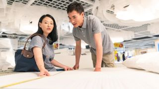 A couple use a yellow tape measure to measure a mattress to ensure it's the right size for them