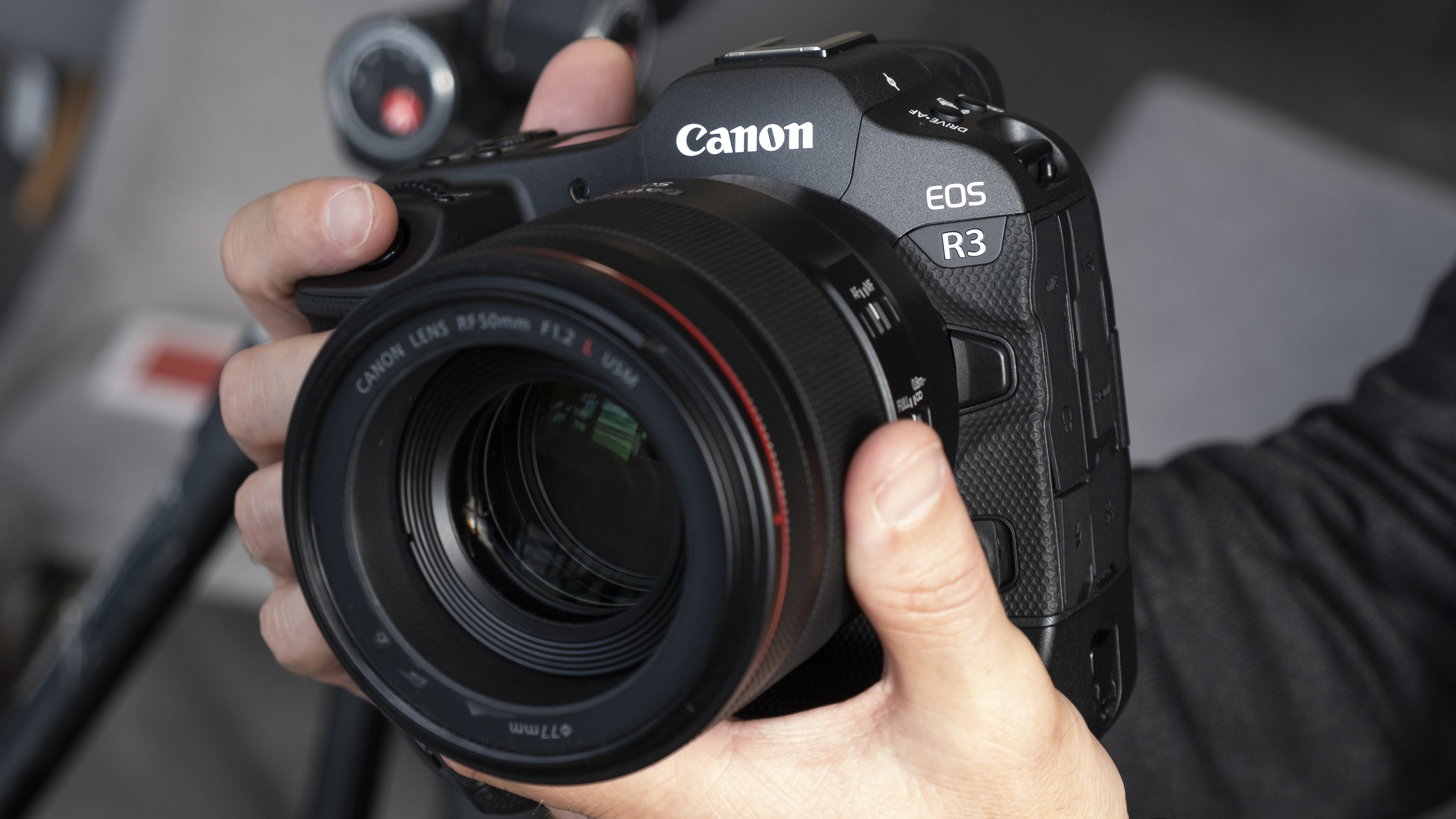 Two hands holding the Canon EOS R3 mirrorless camera