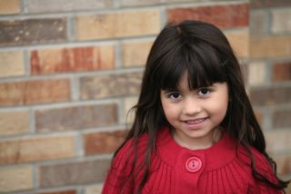 A Latina child smiles.