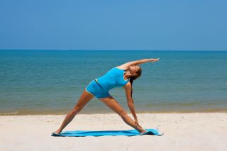 A woman exercises on the beach.