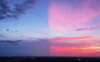 The spectacular colors of this sunset cover only half the sky. A large, distant cloud below the horizon shadows the other half.