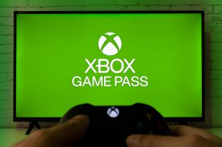 Xbox Game Pass on TV screen with Xbox controller in a man's hands.