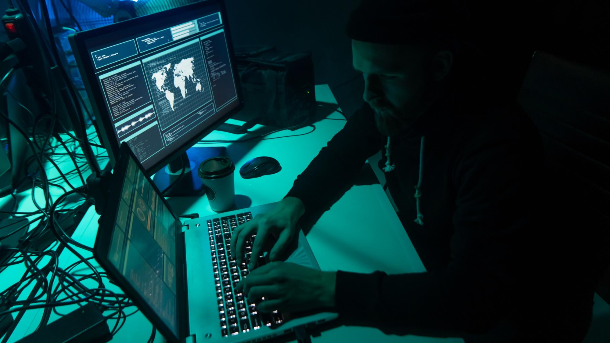 website audit - hacker working on laptop in darkened room