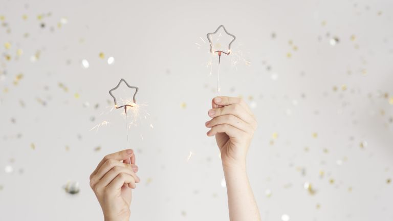 two hands holding sparklers with confetti