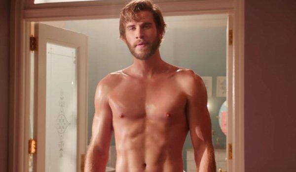 Isn't It Romantic Liam Hemsworth stands in a doorway shirtless