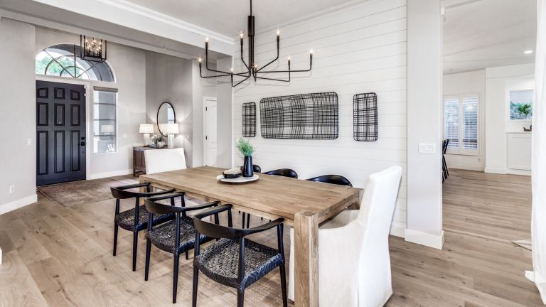 farmhouse kitchen dining table with black chairs and black chandelier