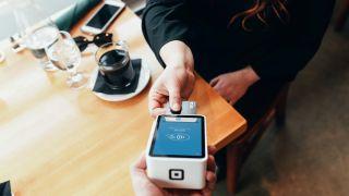 Customer paying for service at POS card reader