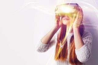 Young woman looks through virtual reality goggles.