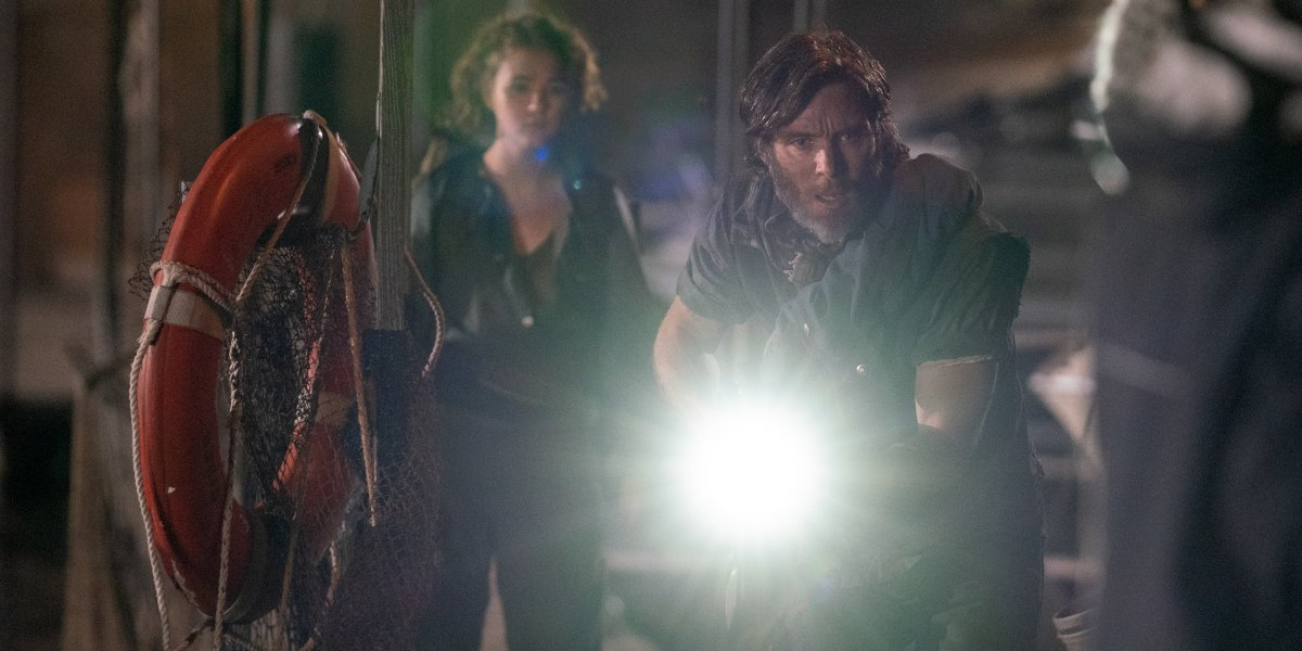 Millicent Simmonds and Cillian Murphy sneaking around a pier at night in A Quiet Place Part II.