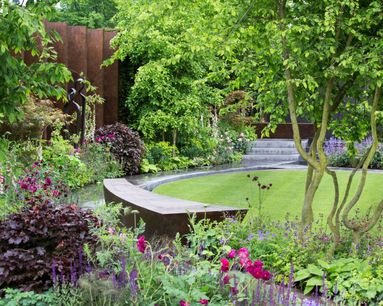 small garden design with circular lawn and curved bench