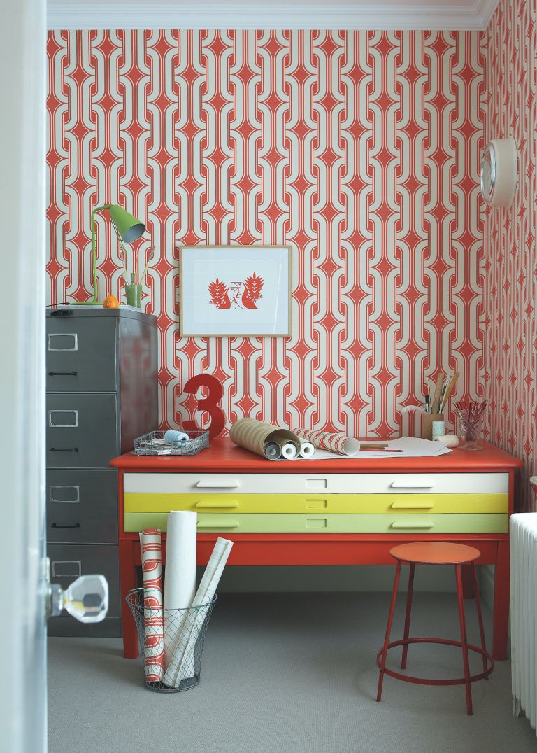 brightly coloured home office with vintage painted desk in multiple colours and red patterned wallpaper