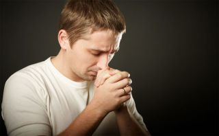 guy prays with his hands folded in front of him