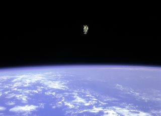 Astronaut Bruce McCandless II floats above Earth, 330 feet (100 meters) from the cargo bay of the space shuttle Challenger, in 1984.