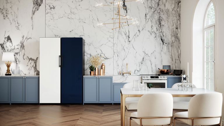 a samsung navy and white fridge freezer in a kitchen with marble effect wallpaper and brass lighting