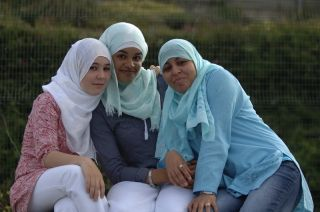 Three happy Muslim women sitting together.