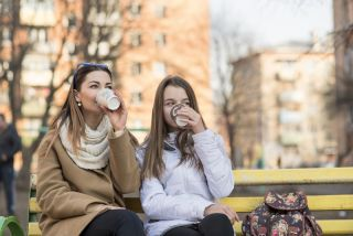 Two women sit on a bench drinking coffee