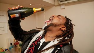 A photograph of Benji Webbe from Skindred pouring a bottle of champagne into his mouth