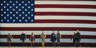 The Suicide Squad group shot in front of a flag