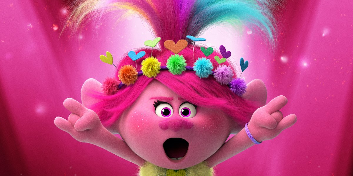 A troll wearing a heart and flower headband rocks out on stage in Trolls World Tour.