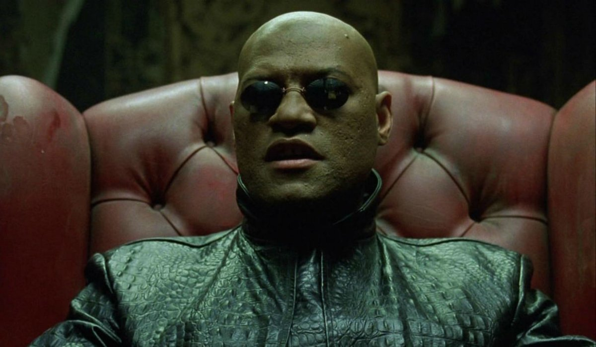 The Matrix Morpheus sits in a chair explaining