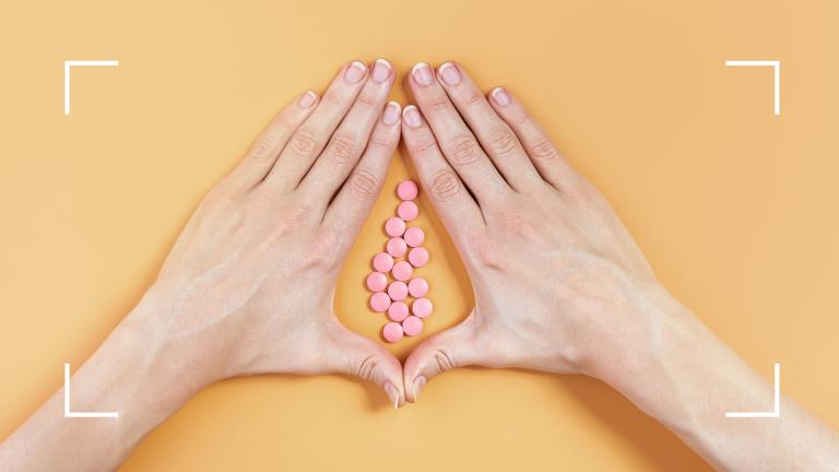 双手环绕橙色背景上的粉红色药丸