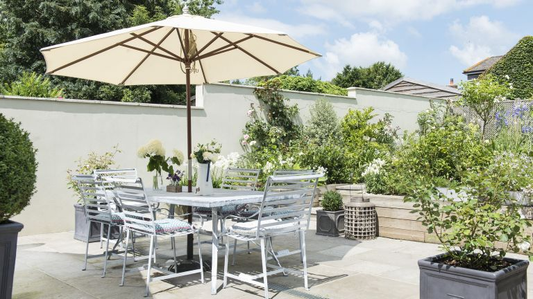 Garden design ideas for a patio in a white colour scheme with table and chairs on a summers day