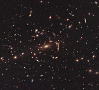 This Hubble Space Telescope photo shows the galaxy cluster MACS J1206, which is warped by gravitational lensing.