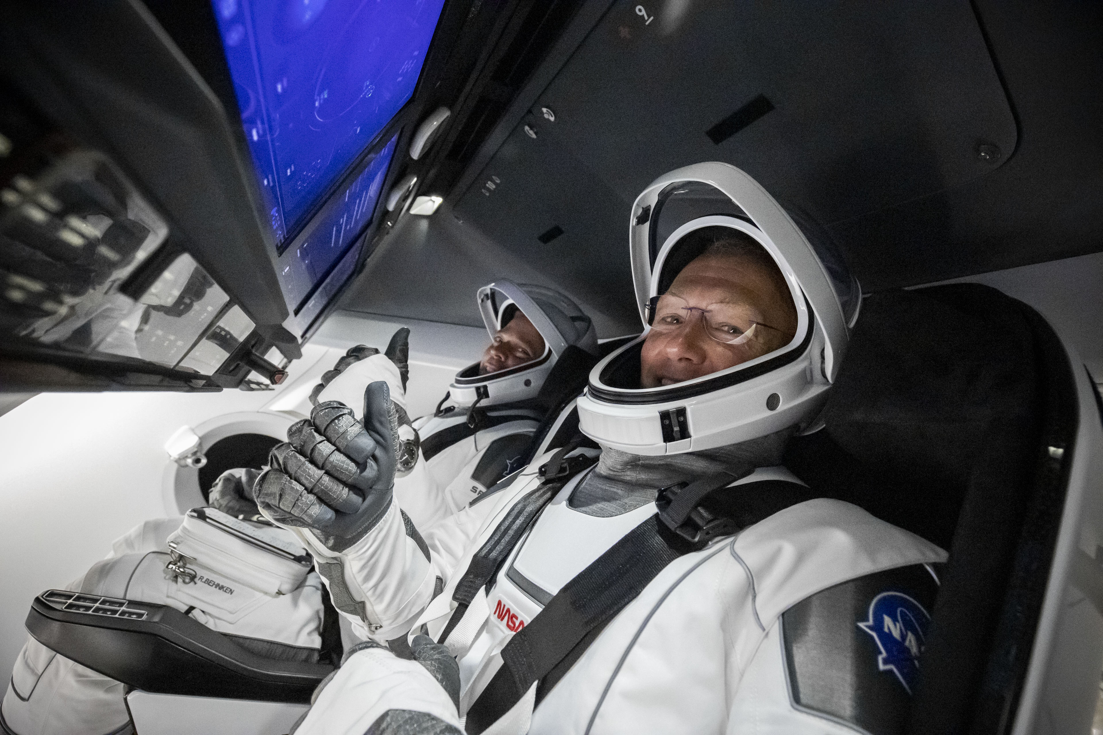 NASA astronaut Doug Hurley gives a thumbs up as he and his Demo-2 crewmate Bob Behnken sit inside the capsule ahead of their second launch attempt on May 30, 2020.