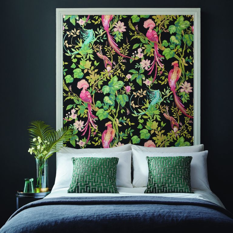 Bright green and pink nature-inspired wallpaper mimics headboard in dark bedroom space