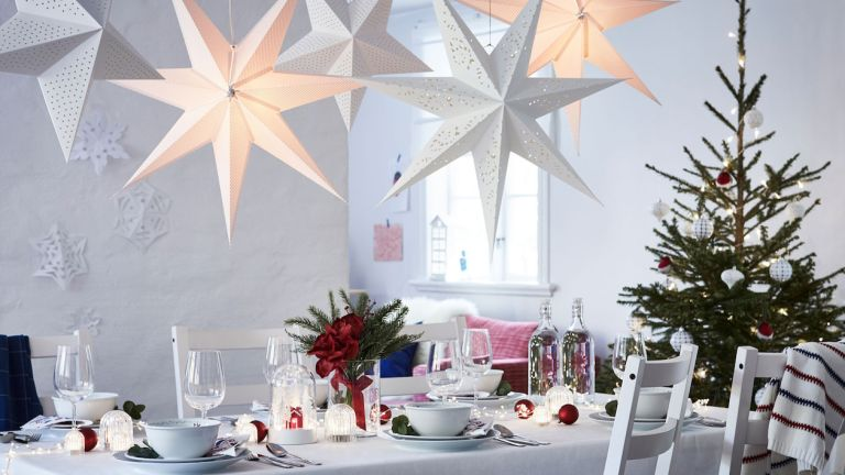 Ikea Christmas dining table decorated for Christmas with a Scandi theme and LED star lights overhead