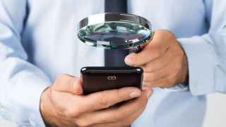 Man using a magnifying glass to look at a smartphone