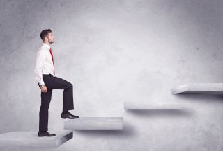 A man in business clothes climbs up a staircase.