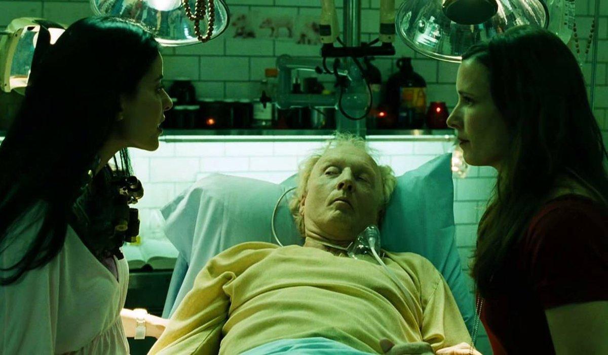 Bahar Soomekh and Shawnee Smith stand beside Tobin Bell's hospital bed in Saw III.