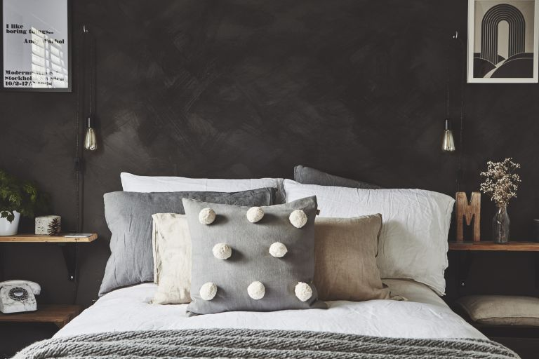 Storage ideas for small bedrooms: Bed with white bed covers and pom pom cushion against a dark concrete-effect wall, with handmade wooden shelves as bedside storage