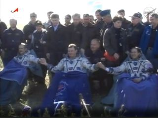 The International Space Station's Expedition 35 crewmembers pose for a crew photo after landing their Soyuz capsule on the sunny steppes of Kazakhstan on May 14, 2013 (May 13 EDT). From left are: Canadian astronaut Chris Hadfield, Russian cosmonaut Roman