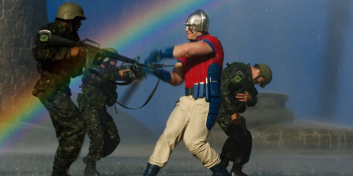 Peacemaker beats up soldiers with rainbow in the background The Sucide Squad