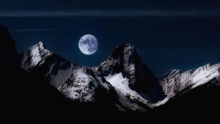 A photograph of a full moon above mountains, taken in New Sarepta, a hamlet in Alberta, Canada.