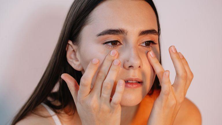 woman applying eye cream under eyes