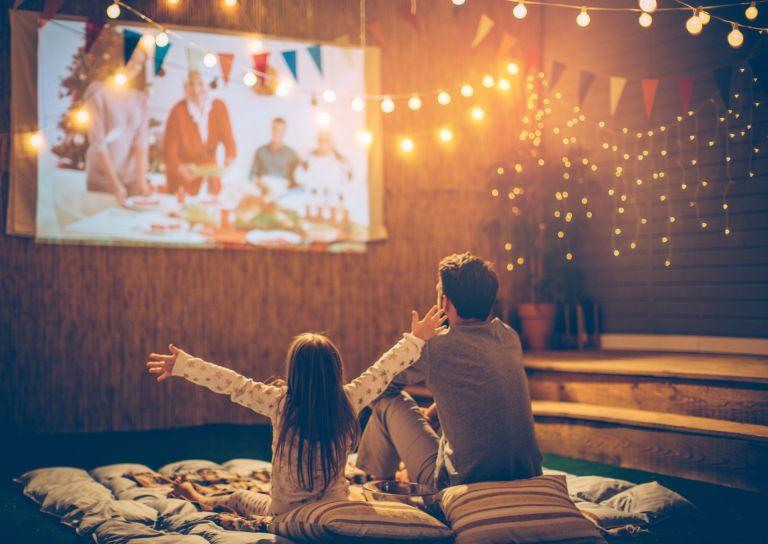outdoor projector screen: Dad and daughter in garden watching movie