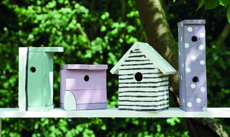 How to build a birdhouse: Line of bird houses in a garden from Pallet wood projects book by CICO Books