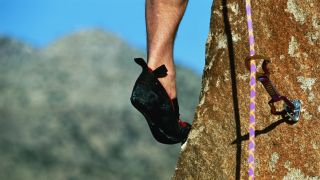 A close up of a climber's shoe on a rock
