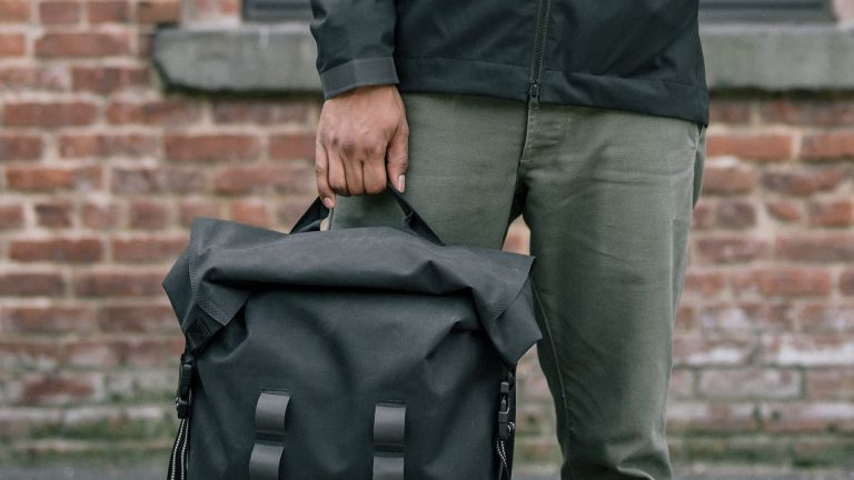 Man stood holding the Chrome Industries Urban Ex Rolltop 2.0 backpack