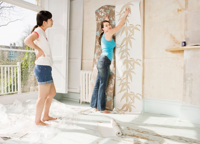 woman deciding on which peel-and-stick wallpapers to place on the wall